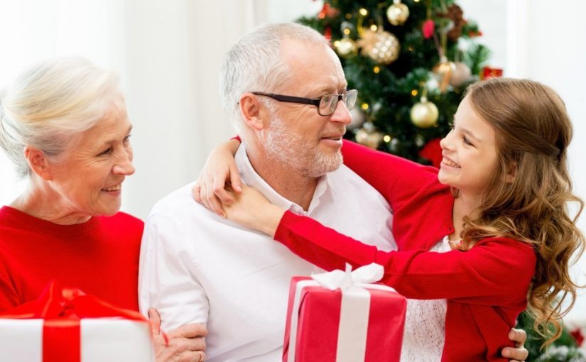 Bedsteforældre med gaver på skødet og deres barnebarn tæt på
